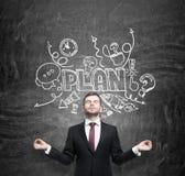De meditatieve zakenman droomt over de bouw van een businessplan voor bedrijfsontwikkeling De schets van het businessplan wordt g Royalty-vrije Stock Afbeeldingen