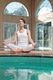 De mediterende zitting van de vrouw in lotusbloempositie stock afbeelding
