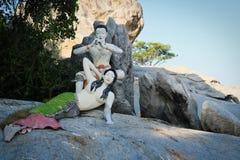 De meermin zit op een rots en achter het een fluitspeler stock foto's