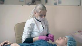 De meester behandelt meisje geschilderde wenkbrauwen met folie in kliniek stock footage