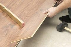 de meester in blauwe handschoenen maakt het leggen floorboard er is een niveau en rubberhamer stock afbeelding