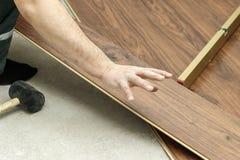 de meester in blauwe handschoenen maakt het leggen floorboard er is een niveau en rubberhamer royalty-vrije stock afbeelding