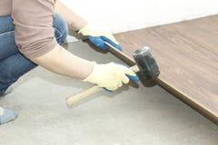 de meester in blauwe handschoenen maakt het leggen floorboard er is een niveau en rubberhamer stock foto's