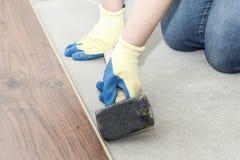 de meester in blauwe handschoenen maakt het leggen floorboard er is een niveau en rubberhamer royalty-vrije stock foto's