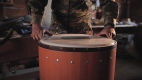 De meester in een privé fabriek verzamelt trommel Installeert plastiek en rand stock footage