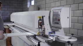 De meester gebruikt industriële machine om randen van spaanplaat in workshop van meubilairinstallatie te verwerken stock video