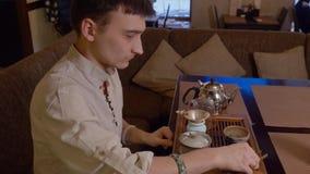 De meester giet warm water in kom en spoelingen voor thee het brouwen aan Japanse traditie stock videobeelden