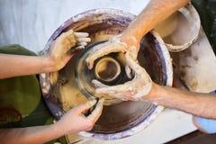 De meester helpt de student om pot van klei te maken De Hulpmiddelen en het Wiel van de Ambacht van pottenbakkers stock afbeeldingen