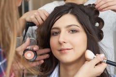 De meester legt borstelpoeder op het gezicht van het meisje op, voltooit de dagsamenstelling in een schoonheidssalon stock foto
