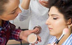 De meester legt borstelpoeder op het gezicht van het meisje op, voltooit de dagsamenstelling in een schoonheidssalon stock fotografie