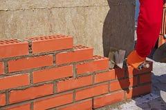 De meester met de troffel zet de rode baksteen royalty-vrije stock foto