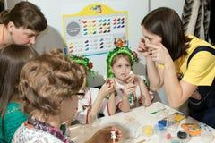De meester onderwijst de kinderen hoe te om speelgoed te maken Stock Afbeeldingen