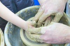 De meester onderwijst het kind, een student van aardewerk Hulp uit klei op een Pottenbakker ` s de te maken rijdt een kruik Royalty-vrije Stock Foto's