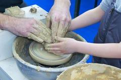 De meester onderwijst het kind, een student van aardewerk Hulp uit klei op een Pottenbakker ` s de te maken rijdt een kruik Stock Afbeeldingen