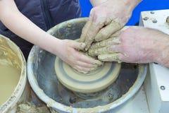 De meester onderwijst het kind, een student van aardewerk Hulp uit klei op een Pottenbakker ` s de te maken rijdt een kruik stock fotografie