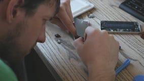 De meester ontmantelde de gebroken telefoon voor vele kleine details, onderzoekt hen 3840x2160 4K stock videobeelden