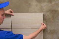 De meester in overall zet keramische tegels stock foto's