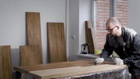 De meester past lak op een oppervlakte van toe houten spaties in een workshop, houdend fles met in hand vloeistoffen stock video
