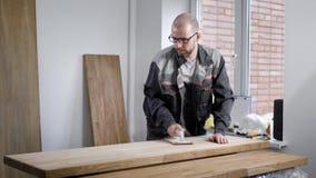 De meester past lak op een oppervlakte van toe houten spaties in een workshop, houdend fles met in hand vloeistoffen stock footage