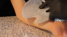 De meester past de tatoegeringsschets op het wapen toe stock footage