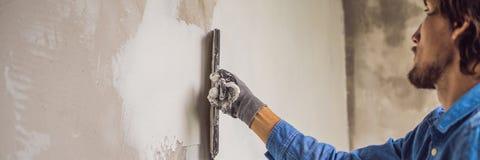De meester past witte stopverf op een muur toe en smeert door stopverfmes in een ruimte van het vernieuwen van huis in dagbanner stock afbeelding