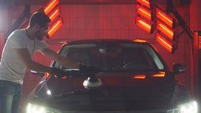 De meester poetst de auto in een autoworkshop op stock videobeelden