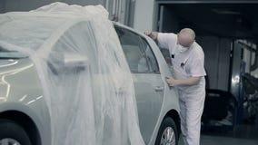 De meester poetst de bumper met een doek op stock footage