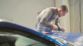 De meester poetst de diepe blauwe sportwagen via poetsmiddelmashine in op een autoworkshop Royalty-vrije Stock Fotografie