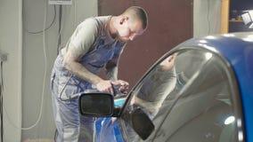 De meester poetst de diepe blauwe sportwagen via poetsmiddelmashine in op een autoworkshop Royalty-vrije Stock Afbeeldingen