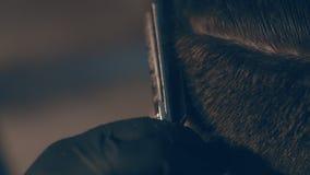 De meester snijdt haar en de baard van mensen in de herenkapper, kapper maakt kapsel voor een jonge mens stock videobeelden