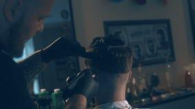 De meester snijdt haar en de baard van mensen in de herenkapper, kapper maakt kapsel voor een jonge mens stock footage