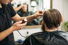 De meester snijdt haar en de baard van mensen in de herenkapper, kapper maakt kapsel voor een jonge mens royalty-vrije stock afbeeldingen