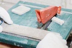 De meester snijdt de tegels op de zaag reparatie van flats en huizen stock fotografie
