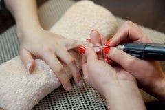 De meester van de manicure zaagt en maakt een spijkervorm tijdens de procedure van spijkeruitbreidingen met vast gel Royalty-vrije Stock Fotografie