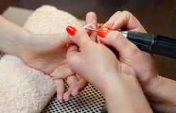 De meester van de manicure zaagt en maakt een spijkervorm tijdens de procedure van spijkeruitbreidingen met vast gel in de schoon Stock Afbeeldingen