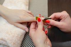 De meester van het nagellak zet een fixatief op de vinger alvorens de spijkers te maken gelatineren Stock Foto