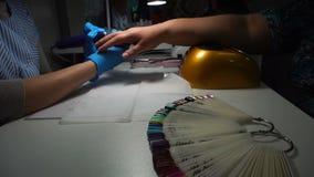 De meester van de manicure maalt de spijkers met een machine, stock videobeelden