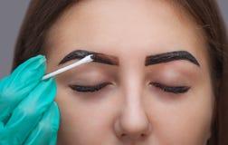 De meester verbetert make-up, geeft het vorm en kleurt de wenkbrauwenhenna in een schoonheidssalon, Kuuroord Stock Foto's