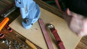 De meester verzamelt leerriem Op bruine houten die lijst met hulpmiddelen en toebehoren wordt verspreid stock video