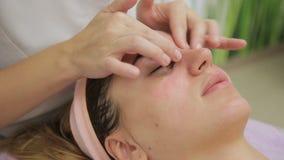 De meester voert gezichtsmassage met cirkelbewegingen rond ogen uit stock footage
