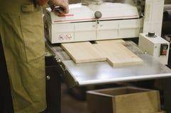 De meester werkt aan een vlakslijpenmachine in de timmerwerkworkshop royalty-vrije stock afbeelding