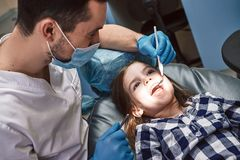 De meilleures dents, une meilleure sant? r Dentiste examinant des dents du ` s de petite fille dans la clinique image libre de droits