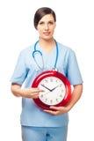 De meisje-arts toont een vinger op een wekker. Royalty-vrije Stock Afbeelding