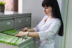 De meisje-beheerder van de medische kliniek zoekt een geduldige kaart in de lade van het rek stock afbeelding