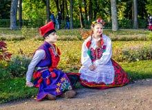 De meisje en jongensleden van de Poolse volksdans GAIK in traditionele kostuums Stock Foto's