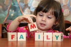 De meisje en stuk speelgoed kubussen Stock Foto's