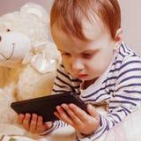 De meisje het letten op beeldverhalen Weinig kindmeisje dat mobiele telefoon in openlucht met behulp van ontspanning, technologie royalty-vrije stock afbeelding
