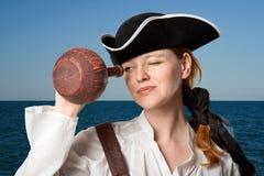 De meisje-piraat kijkt in een kruik tegen het overzees stock afbeeldingen