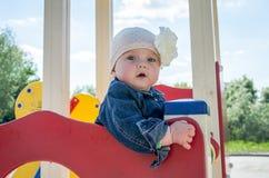 De meisjebaby in de hoed met een bloem en een blauw denimjasje en een rood kleden het spelen in de speelplaats en het glimlachen Stock Afbeeldingen
