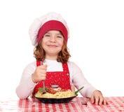 De meisjekok eet spaghetti Stock Afbeeldingen